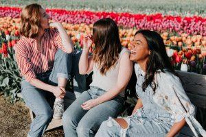 women enjoying perfumed flowers